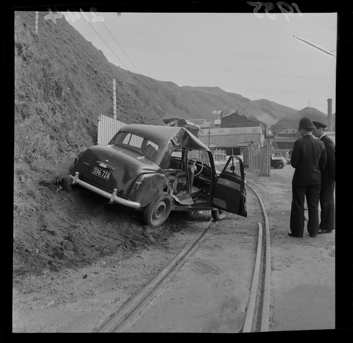 Unidentified police officers looking at a Humber motorcar that has been in an accident, Ngauranga Freezing Works, Wellington