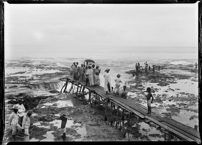 Niueans waiting on a wharf at low tide, during the visit of the HMS Mildura and Lord Ranfurly