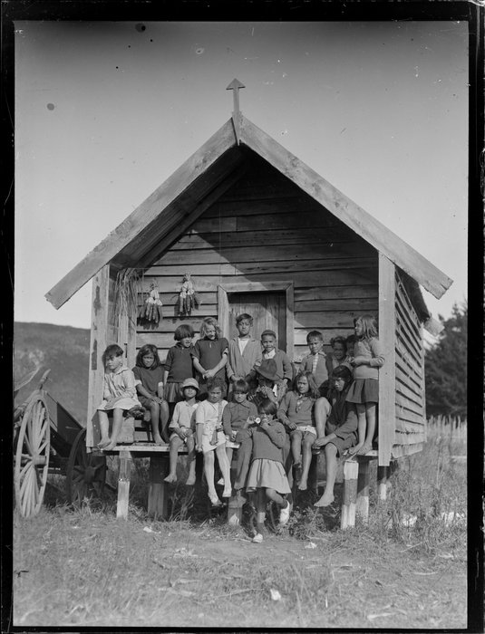 Group of Māori children in front of a storehouse, Korohe marae