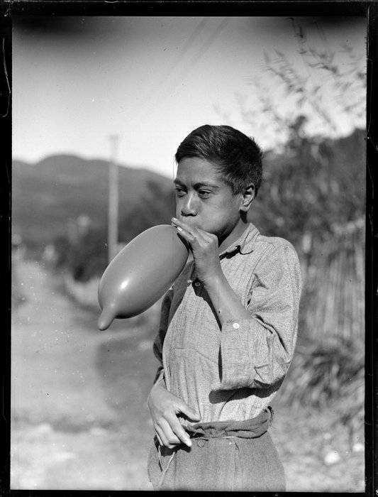 Māori boy, possibly Moetu Otimi, blowing up a balloon, Waikato