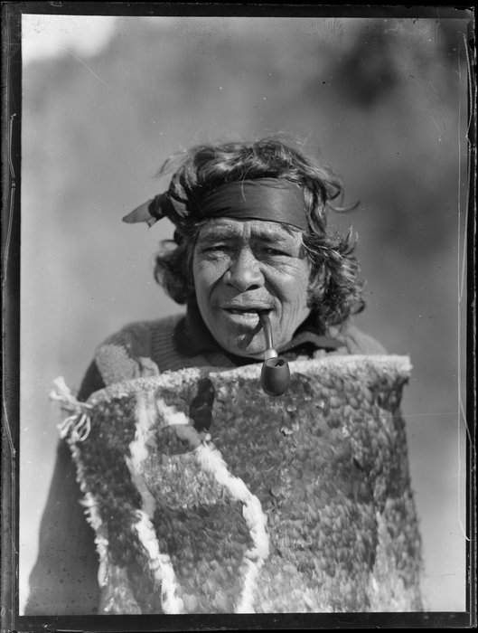 Portrait of Maori kuia Marutuna of Orakei Korako smoking a pipe and wearing a traditional feather cloak