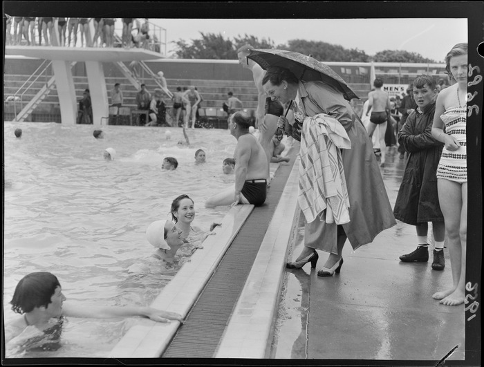An unidentified woman, sheltering under an umbrella and talking to swimmers, Naenae Olympic Swimming Pool, Lower Hutt