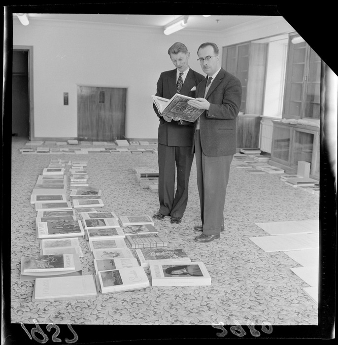 Tony Murray-Oliver with an unidentified man looking at a book with other books for the Alexander Turnbull Library laid out on the floor, Wellington