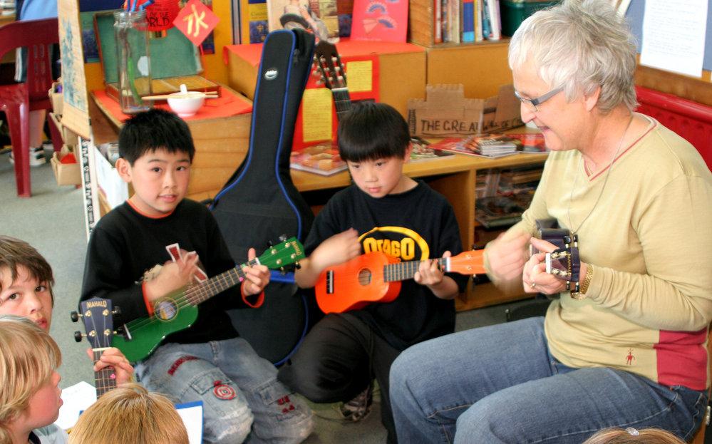 Teacher and children with ukeleles