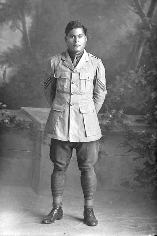 Full length portrait of Corporal Harry, probably (private in the roll) Purie Dave Harry, Reg No 16/1371, of the 3rd Maori Contingent, Rarotongans, New Zealand Maori Pioneer Battalion.