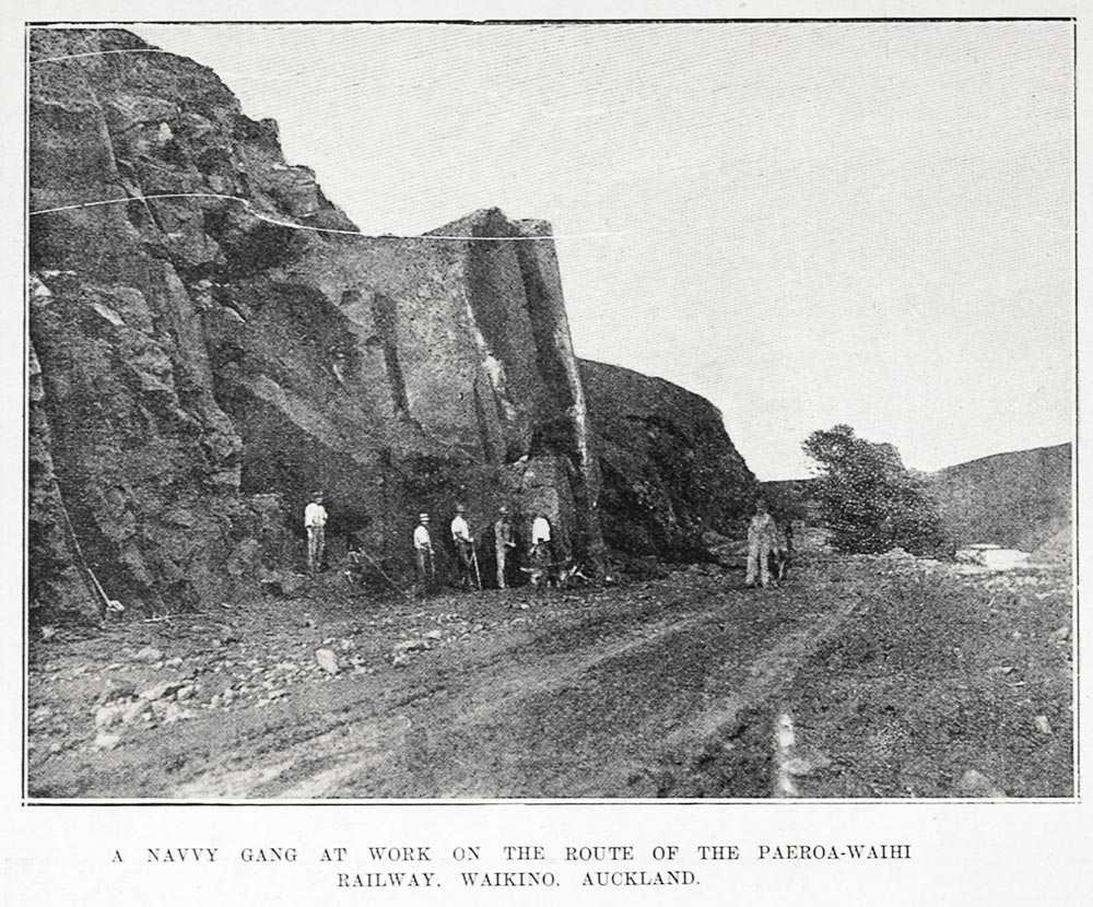 A NAVVY GANG AT WORK ON THE ROUTE OF THE PAEROA-WAIHI RAILWAY. WAIKINO. AUCKLAND