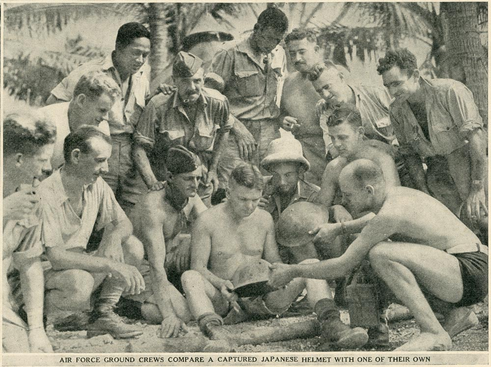 AIR FORCE GROUND CREWS COMPARE A CAPTURED JAPANESE HELMET WITH ONE OF THEIR OWN