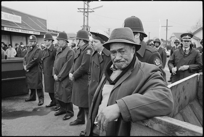 Percy Bush, uncle of the captain of the New Zealand Maori rugby team, standing by police as anti-apartheid demonstrators march by