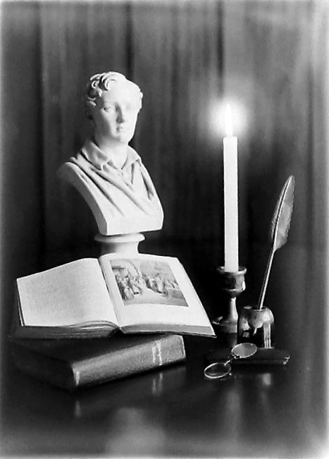 Still life of books, bust of Lord Byron, candle.