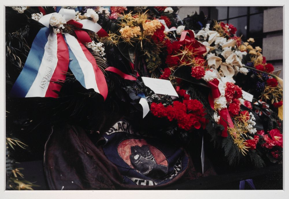 Denis O'Reilly's Black Power jacket and wreaths on coffin of Norman Kirk