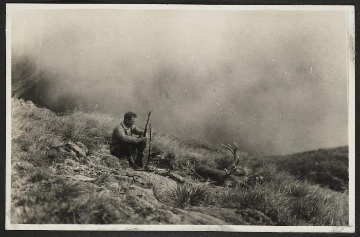 Arthur Gregg on hillside with gun and dead deer