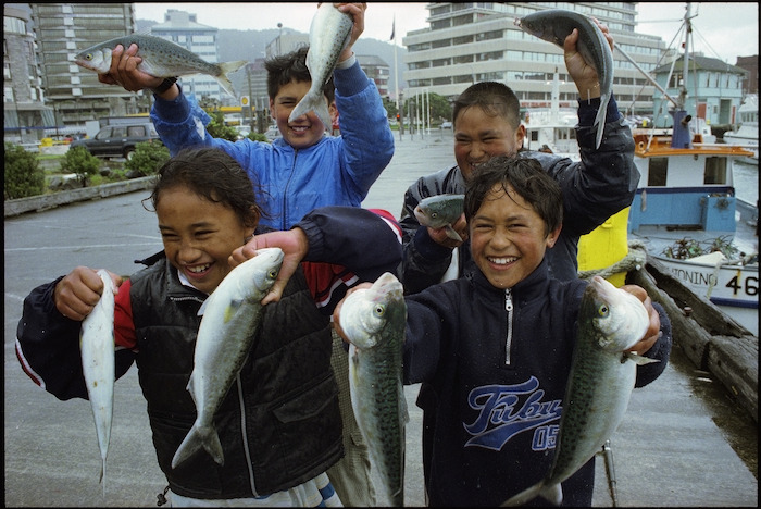 Four children hold up kahawai caught at Queens Wharf, Wellington - Photograph taken by Ross Giblin