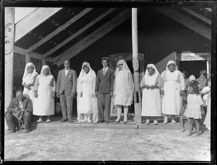 Brides, grooms and Awhina of the Rātana church in front of a meeting house, Korohe marae