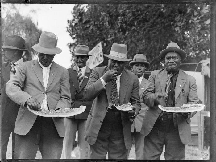 Group of Maori men eating watermelon, location unidentified