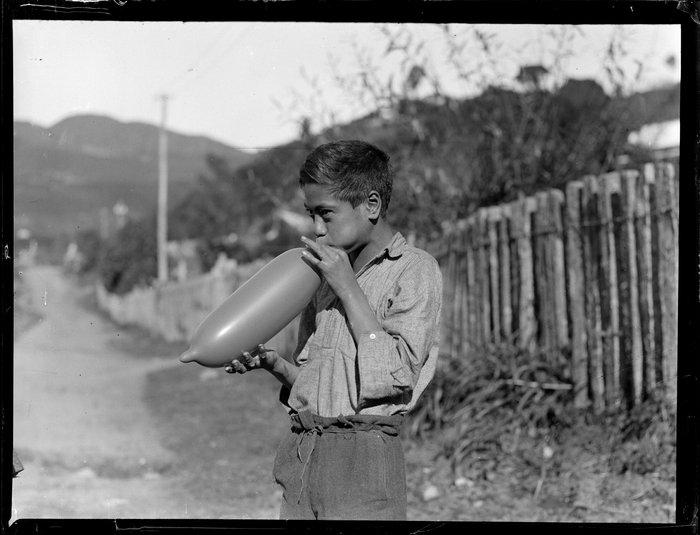 Māori boy, possibly Moetu Otimi, blowing up a balloon, Waikato