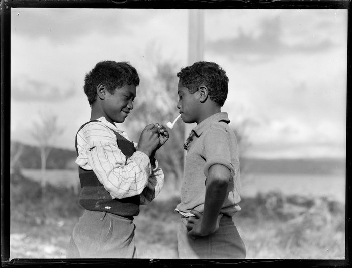 Māori boy lighting the pipe for his young friend, Waikato