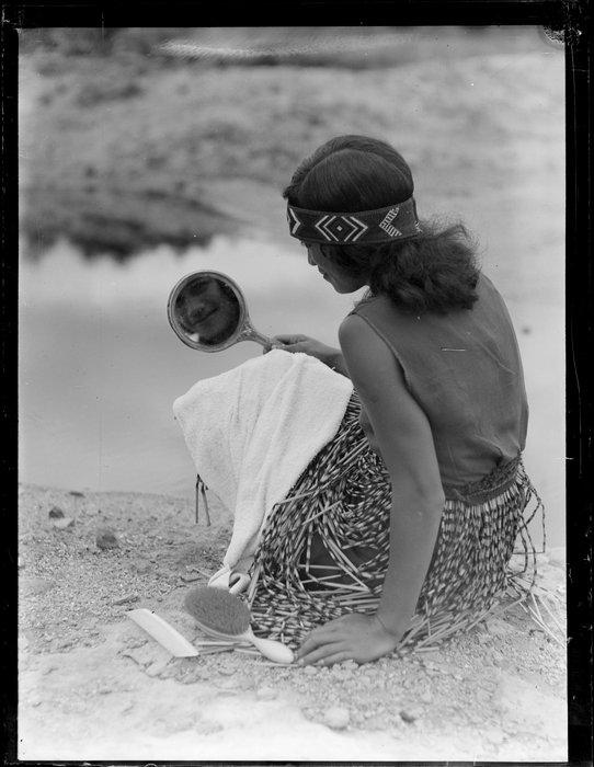 A Maori woman grooming herself by the river, Waikato