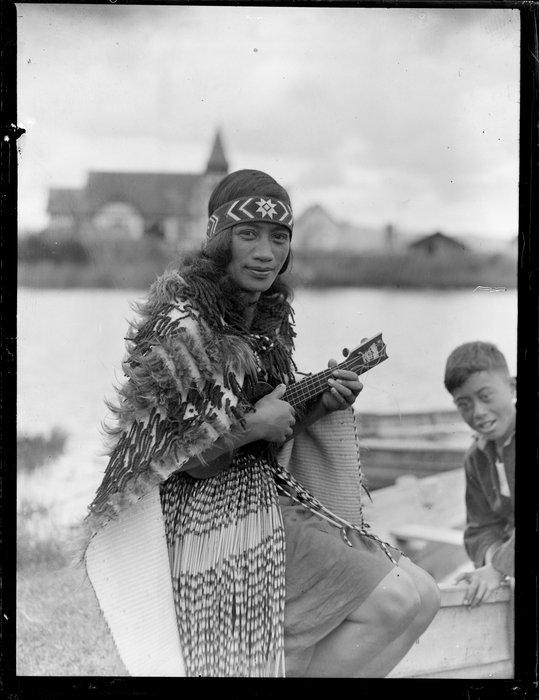 Maori woman in costume playing the ukelele, location unidentified