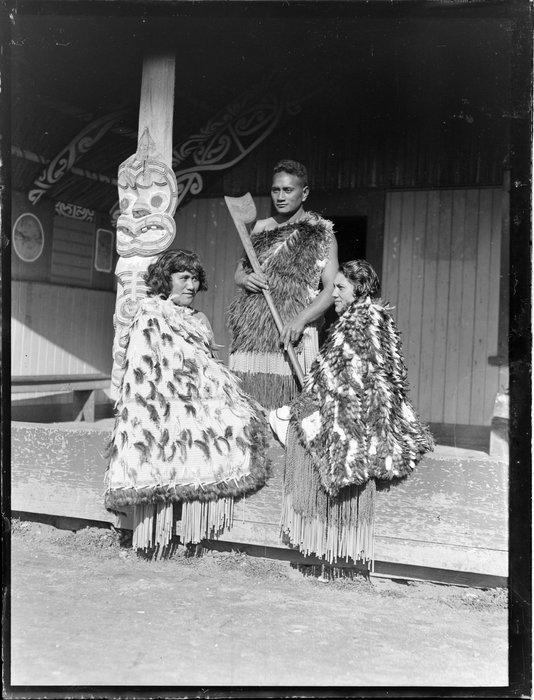 Pura Konui, Mihihi Kuru and Tarihira Mihinui-Northcroft dressed in kakahu and piupiu, at Otūkou marae, Lake Rotoaira