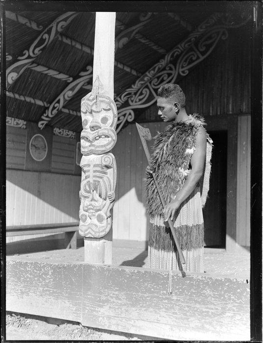 Portrait of Minihi (Jack) Kuru holding a tewhatewha at Otūkou marae, Lake Rotoaira