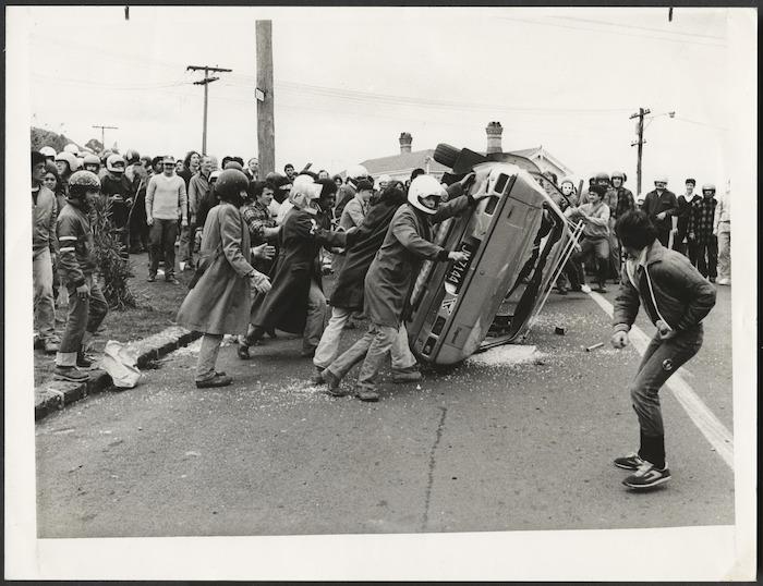 Anti Springbok tour demonstrators overturn a car, Auckland, New Zealand - Photograph taken by an Auckland Star photographer