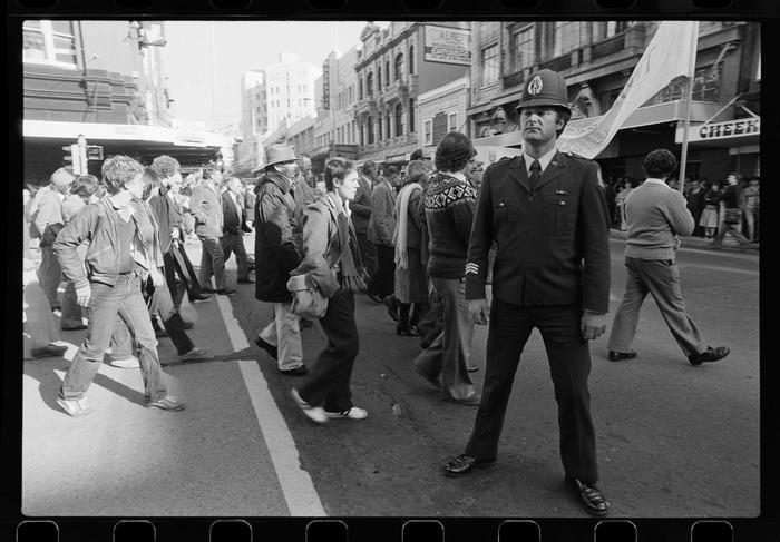 Policeman facing camera, protesters walking past behind him