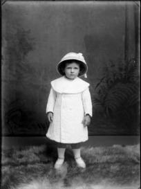 Studio portrait of unidentified small girl, wearing a coat and hat, probably Christchurch district