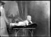 Studio portrait of unidentified unclothed baby, lying on stomach, probably Christchurch district