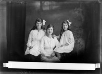Studio portrait of unidentified mother and two girls, woman is wearing spectacles and both girls are wearing ribbons in their hair, probably Christchurch district