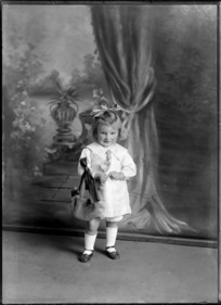 Studio portrait of unidentified small girl, holding a bag, with a ribbon in her hair, probably Christchurch district