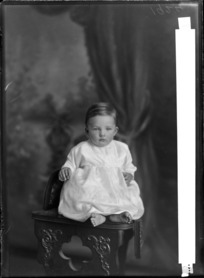 Studio portrait of unidentified small child, sitting on a carved wooden chair, probably Christchurch district