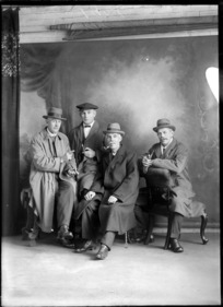 Studio portrait of four unidentified mature men, all wearing long overcoats and holding pipes, probably Christchurch district