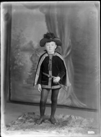 Studio portrait of unidentified boy, wearing a sword costume and frilly hat, probably Christchurch district