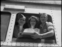 Two repatriated soldiers and a Red Cross worker look out train window at Alexandria on the way to Cairo, World War II - Photograph taken by H Paton