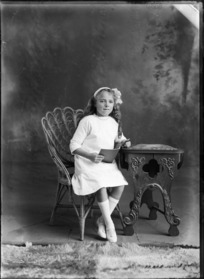 Studio portrait of unidentified girl holding a book, probably Christchurch
