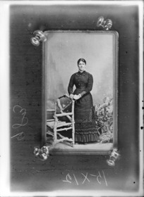 Studio portrait of unidentified woman in photograph pinned to wall
