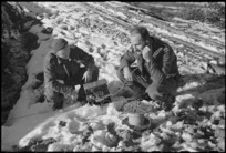 Signallers A McKechie and R J McConway testing ground lines after a snow-storm on the Italian Front, World War II - Photograph taken by George Kaye