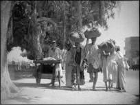 Street scene in Cairo showing local people carrying large bundles on their heads - Photograph taken by George Kaye