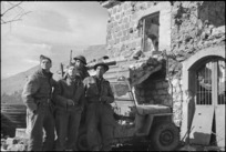 Maori and pakeha soldiers beside damaged building on 5th Army Front, Italy, World War II - Photograph taken by George Kaye