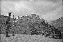 New Zealand provost, J J Morgan, directs traffic at turnoff near Aquafondata, Italy, World War II - Photograph taken by George Bull