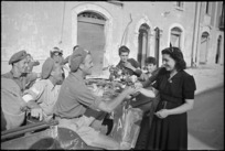 Young woman of Sora, Italy, gives flowers to New Zealanders in World War II - Photograph taken by George Kaye