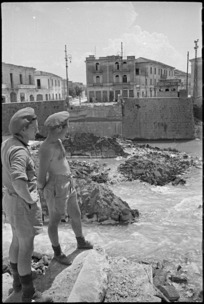 R W Jemison and F J Martin look across a River towards a demolished bridge in Sora, Italy, World War II - Photograph taken by George Kaye