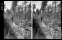 Unidentified man, walking along track in bush area, unidentified location