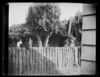 Scene including ponga log fence and unidentified people, Chatham Islands