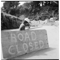 A road worker manning a 'Road closed' sign, 1974.