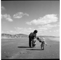 Children and a man playing on a beach, possibly at Raumati