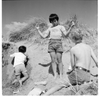 Family playing in sand dunes, possibly at Raumati Beach