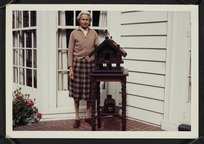 Agnes Isobel Stout with carved Maori artefacts on the porch of her house