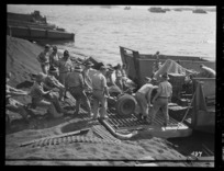New Zealand soldiers loading equipment into landing craft before leaving New Caledonia for the north, during World War II