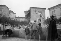 People looking at an undamaged statue, among the ruins of Gessopalena, Italy